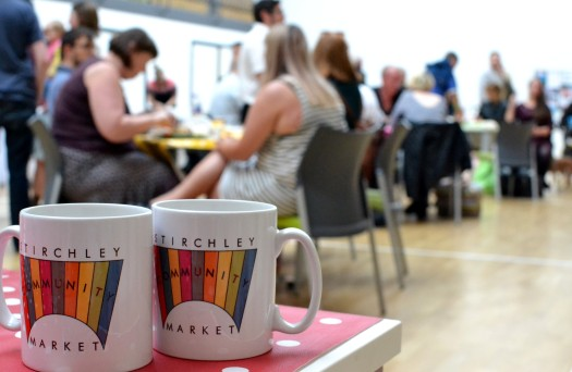 Market mugs in the foreground, and customers sitting around tables in the background