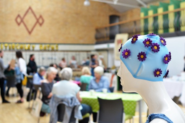 A dummy wearing a swimming cap looks out on Market taking place in the main hall