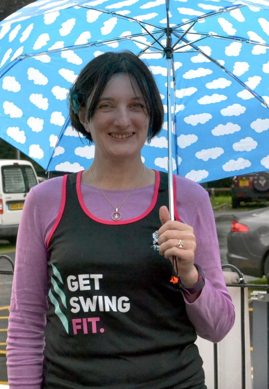 Carola of Swing Fit smiling under an umbrella