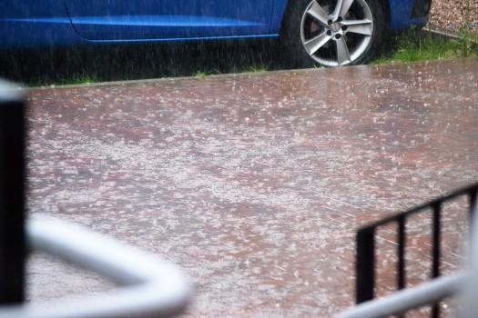 Heavy rain falls on the pavement outside Stirchley Baths