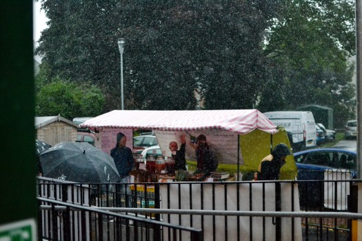Heavy rain falls on the outside Market stall and an umbrella