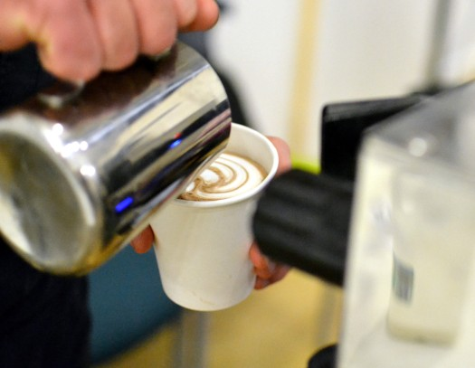 Adding a swirl of milk to a hot drink on the There Goes stall