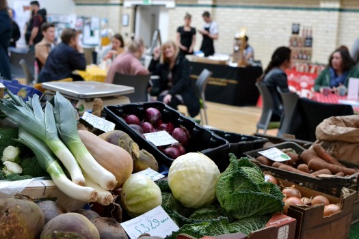 A stall serving fresh veg with Market customers in the hall behind